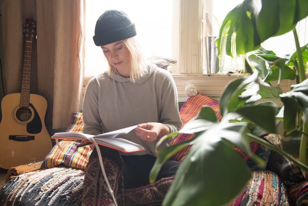 a girl in a black hat sitting and reading her travel journal from Wakeful Travel