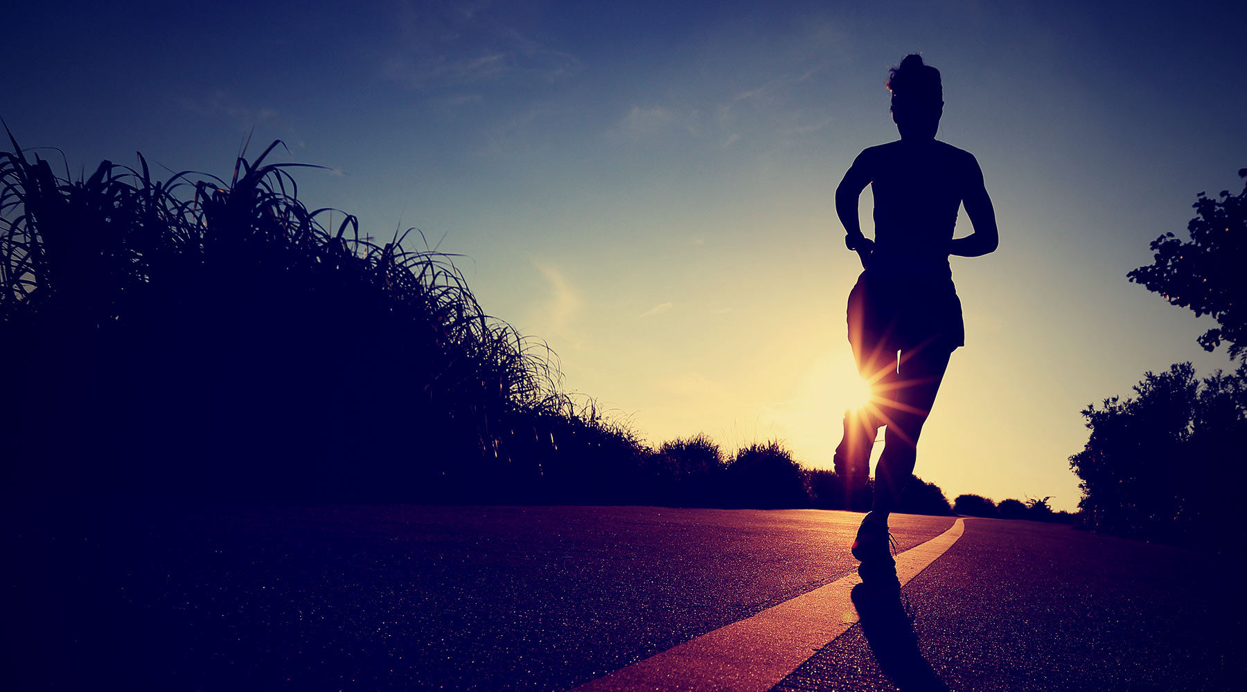 young woman running down road at sunrise