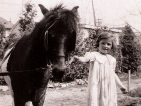 Black and white photo of a child and pony