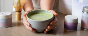 zenmatcha matcha latte oat milk matcha latte in grey bowl. matcha latte being held. bamboo whisk chasen shogun matcha premium matcha artisan matcha