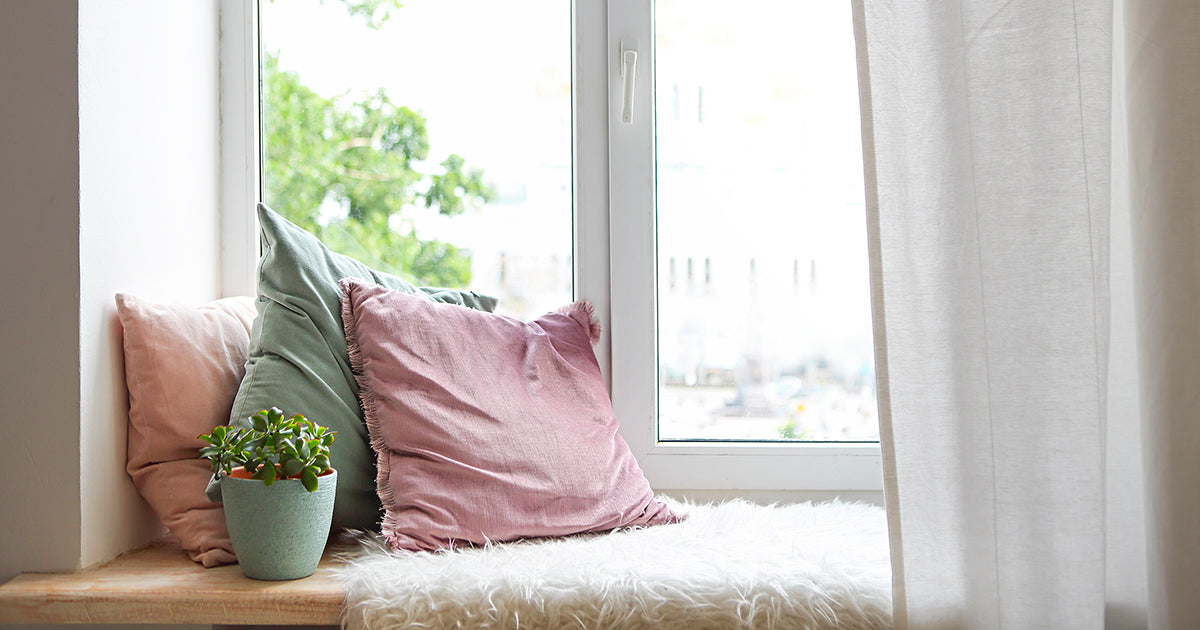 pillows on bench seat by window, calming relaxing wellness