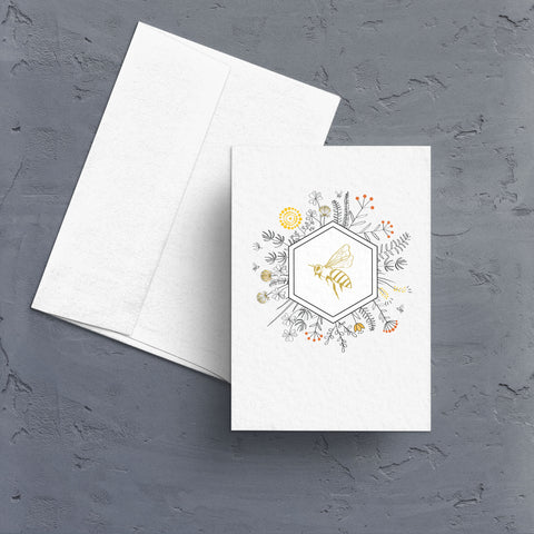 This all-occasion note card features a gold foil bee in the center of a honeycomb hexagon surrounded by wildflowers.  Card is blank inside.