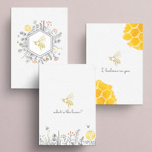 "The buzzworthy assortment of notecards features a gold foil bee in the center.  One card is embellished with a honeycomb corners and says ""I beelieve in you"", another features the bee floating above a wildflower field and says ""what's the buzz"".  The third notecard is the bee inside the honeycomb hexagon with wildflowers.  All note cards are blank inside."