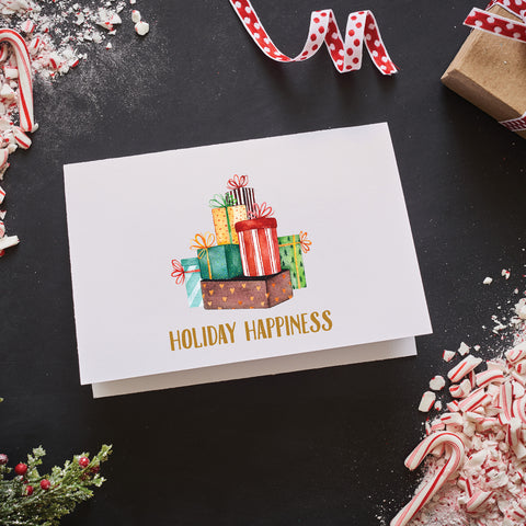 "watercolor image of a pile of Christmas presents is centered above the glitter gold foil text ""holiday happiness"" on the 4-bar folded note card with blank notecard"