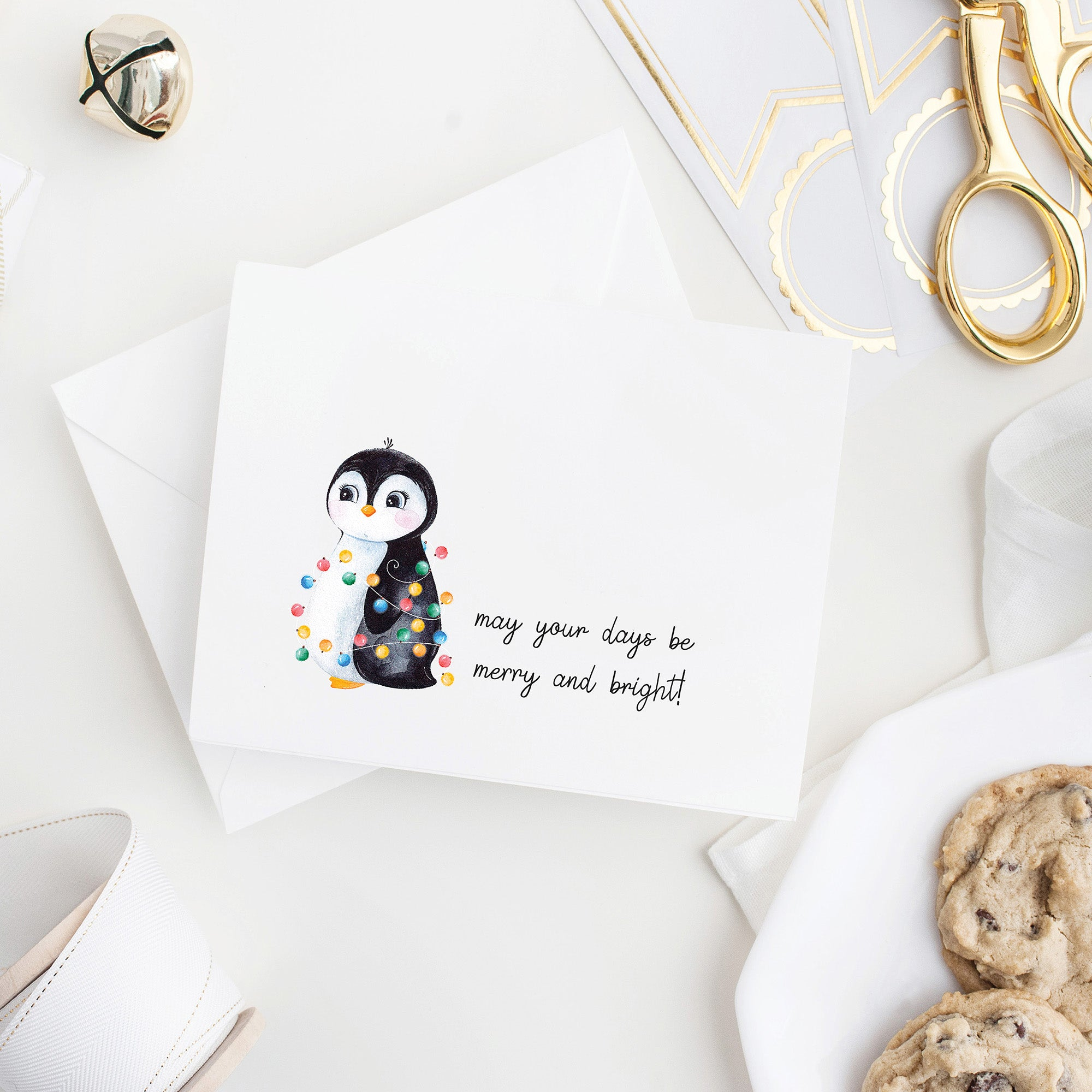 May your days be merry and bright holiday folded note card with watercolor penguin wrapped in string lights on a folded notecard with blank envelope