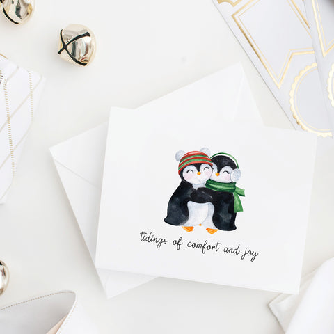 Tidings of comfort and joy with watercolor penguins wearing hats and scarves snuggling on the front of this folded notecard with blank envelope