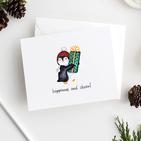 Happiness and cheer features a watercolor penguin presenting a wrapped gift on a folded notecard with blank envelope