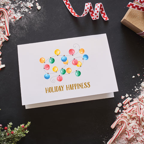 "Glitter gold foil stamped ""holiday happiness"" labels a cute watercolor image of Christmas string lights on this folded note card with blank envelope included"