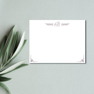 A simple script initial monogram is gently embellished with baroque style scroll elements on this lovely flat notecard by Staccato.