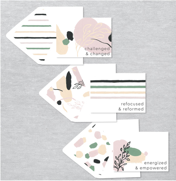 Three folded notecards with motivational messages on top of a watercolor design and beautiful lined envelopes.