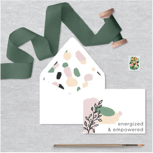 "White folded notecard features ""Energized & Empowered"" on a watercolor designs and a floral envelope lining."
