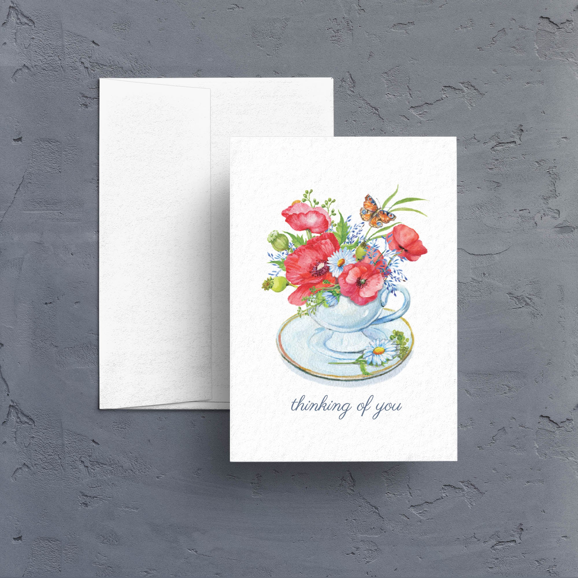 A lovely little all-occasion notecard features beautiful watercolor artwork of a teacup filled with a floral arrangement of poppies and daisies.  Note cards are blank inside.
