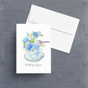 "Send a beautiful ""thinking of you "" card featuring a pretty little tea cup filled with a blue floral arrangement and a pretty blue bird.  Notecards are blank inside."