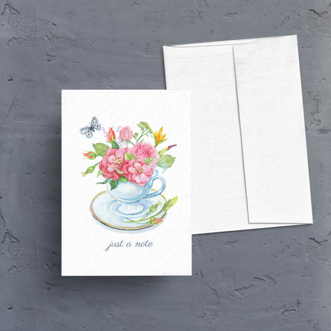 "Pretty watercolor artwork of a teacup holding a pretty pink and yellow floral arrangement with a blue butterfly floating around it.  Captioned with ""just a note"", this is the perfect all occasion note card.  Cards are blank inside."
