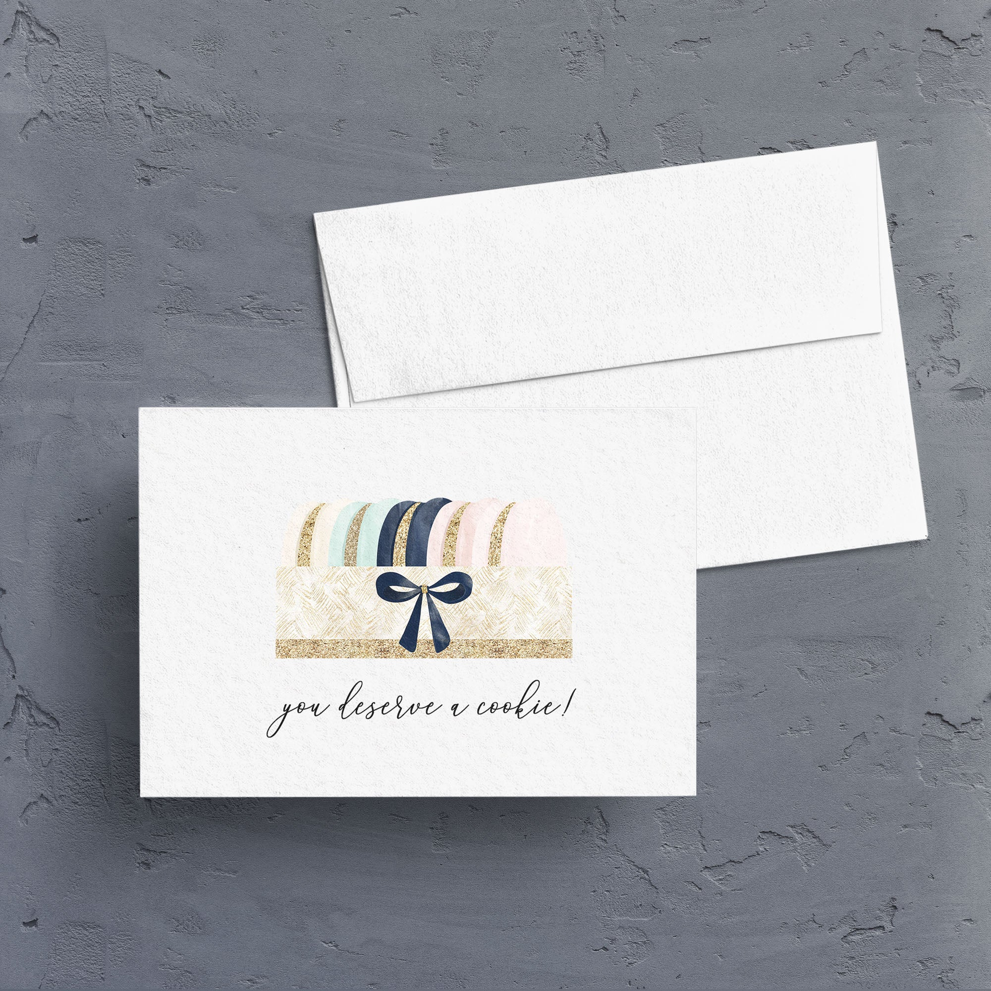 "Pretty watercolor artwork of a box of French Macarons is captioned with ""you deserve a cookie"" is the perfect way to say thank you or congratulations.  Notecards are blank inside."