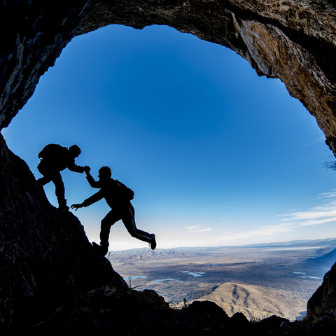 mountain climbers silhouetted against the sky