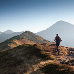Person hiking on top of a mountain with two walking sticks.
