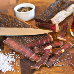 Fresh-cut biltong with various spices and cooking materials surrounding it.