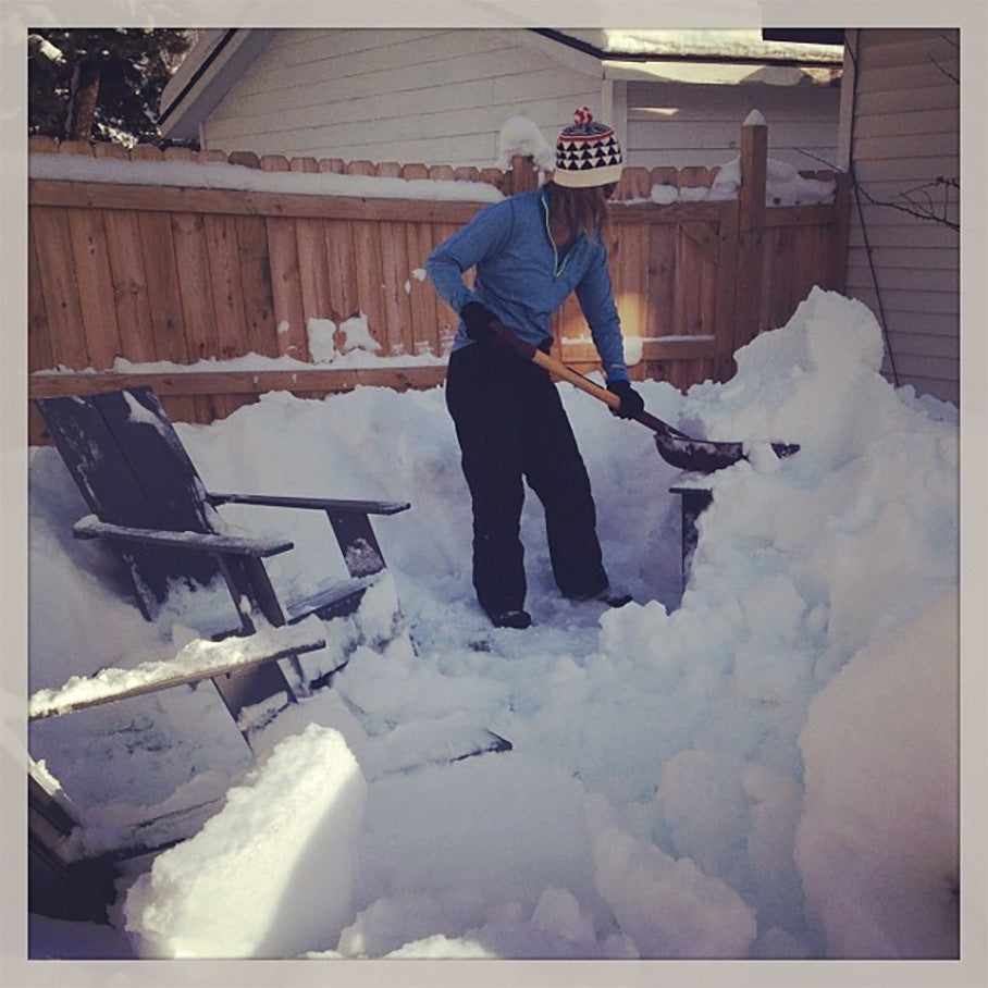 Woman digging chairs out from under snow
