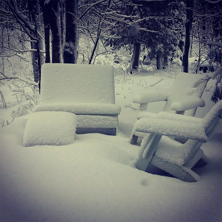 Loll chairs covered in snow in background
