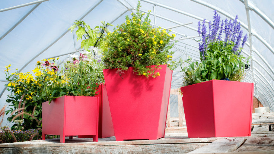 Three red Loll Garden Planters with flowers