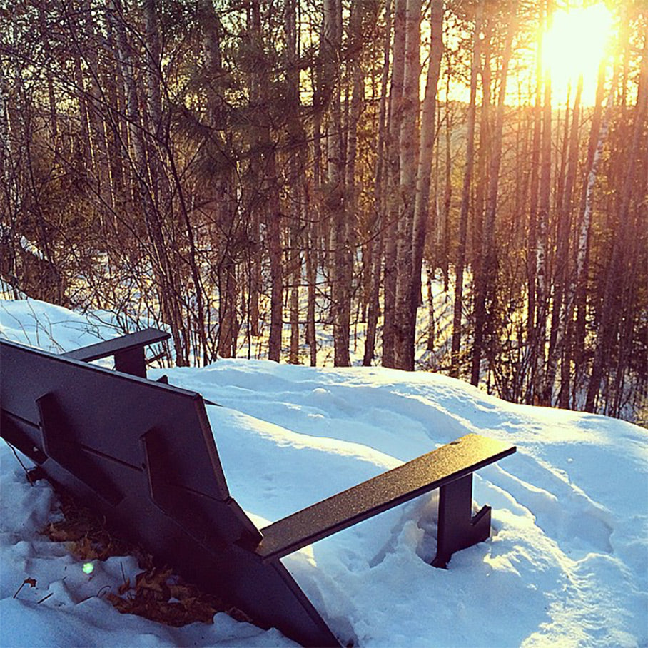 Loll chair covered with snow on trail with sunset