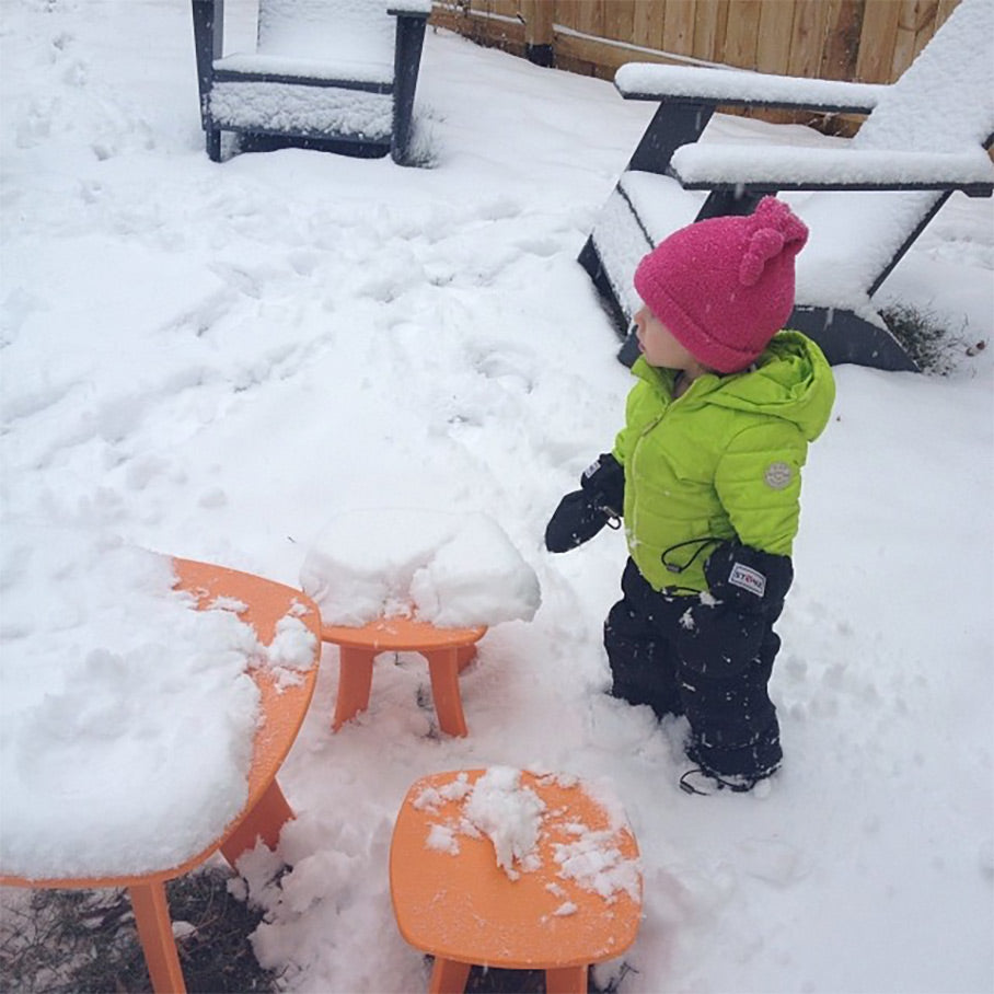 Toddler standing by Loll furniture covered in snow
