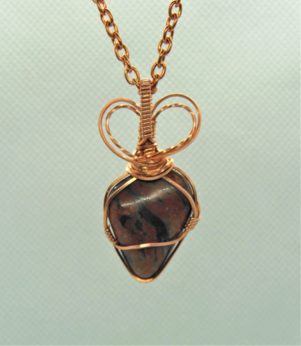Red Feldspar polished stone wrapped in copper wire as a pendant.