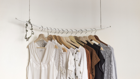 Clothing hanging from a rail in neutral tones