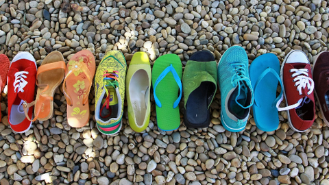 A row of unwanted shoes in a rainbow formation