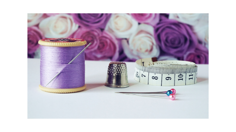 Purple cotton thread, pins, measuring tape, thimble