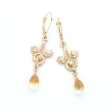 Gold filigree hand carved dangle earring with three swirls containing diamonds and faceted citrine dropout the bottom