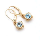 Handmade delicate gold earring with faceted sky blue topaz in center