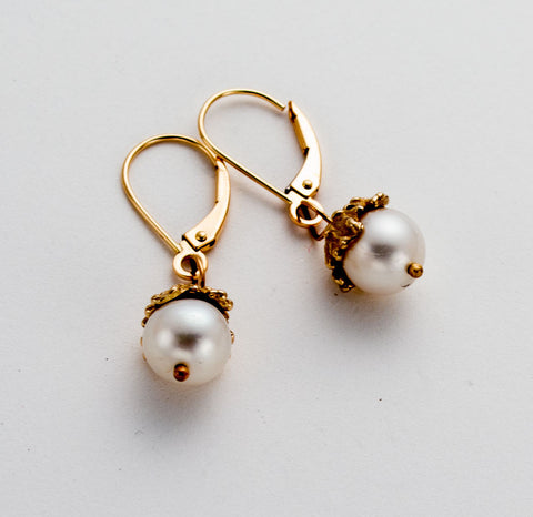 Handmade pearl drop earring with delicate filigree cap over the top of the pearl