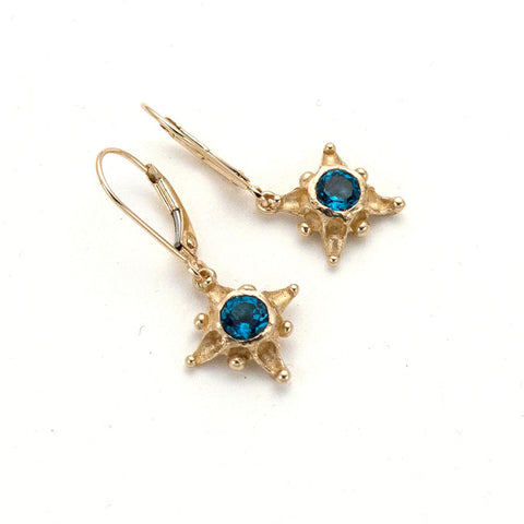 Tiny 14 karat gold star drop earrings with London blue topaz center