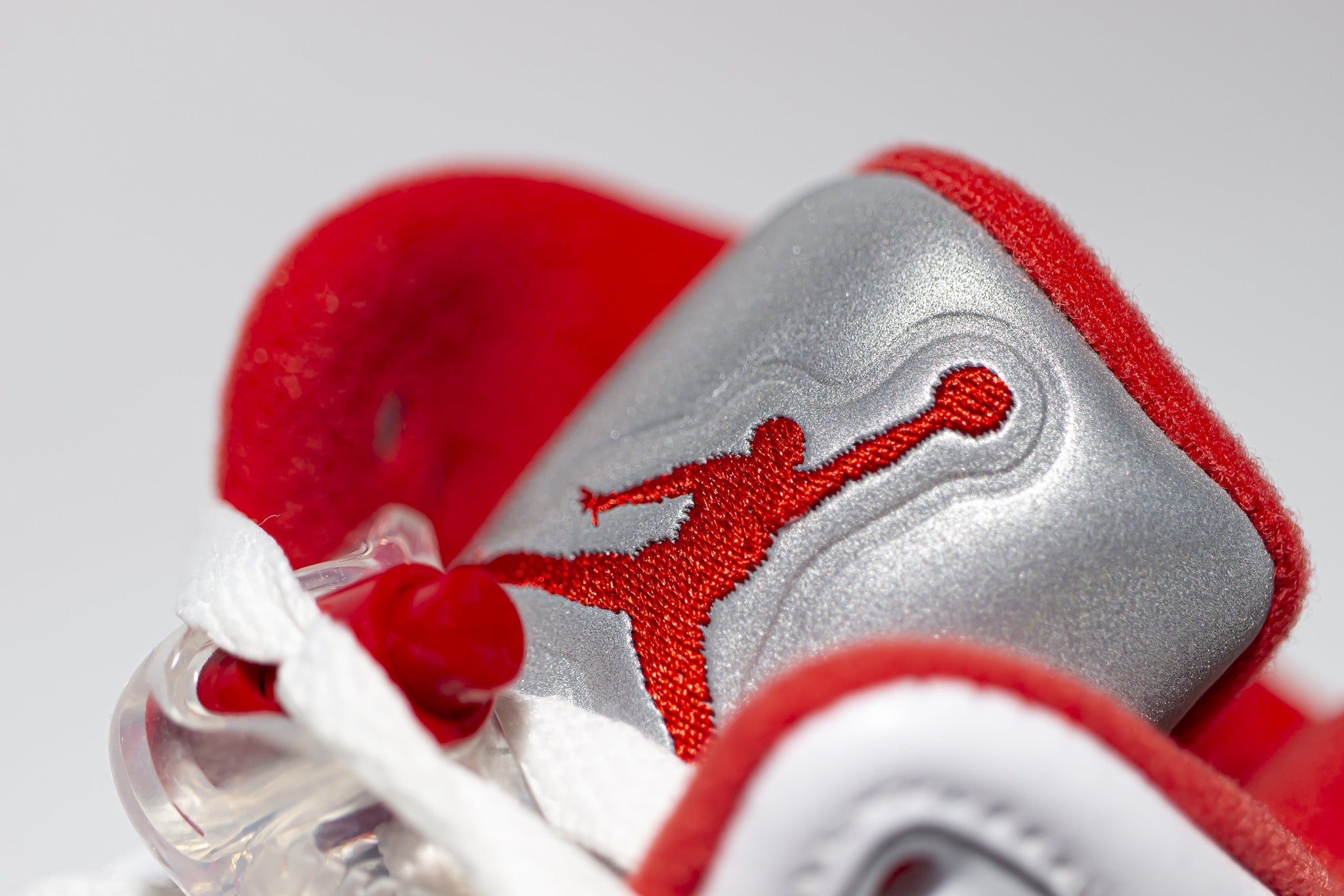 Close up view of embroidered red jumpman logo on 3m reflective sneaker tongue