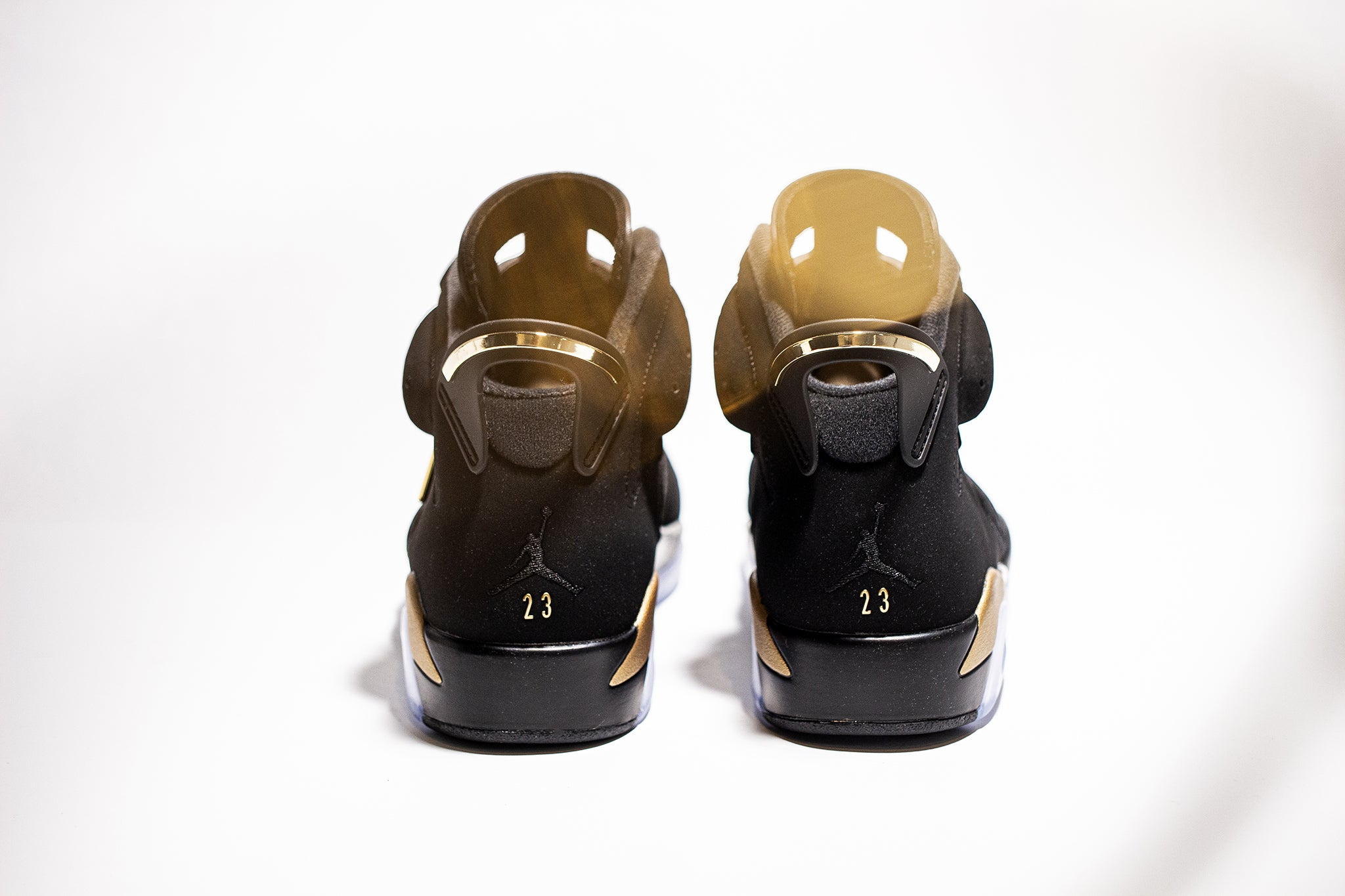 Reverse side view of a pair of black gold Jordan 6 sneakers