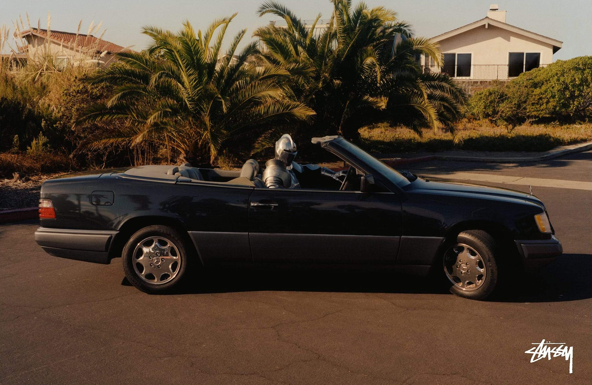 Person dressed in armor driving a black Mercedes SL parked in a cul-de-sac for Stussy photoshoot