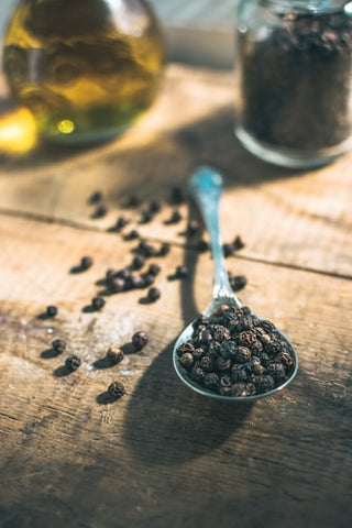 A spoon full of black peppercorns, a rich source of caryophyllene.