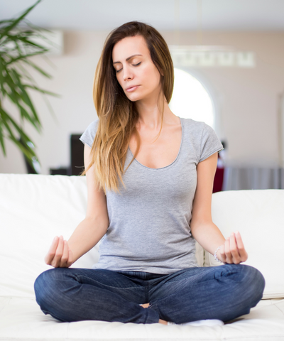 A woman using a breathing and meditation technique to help relieve high anxiety naturally.
