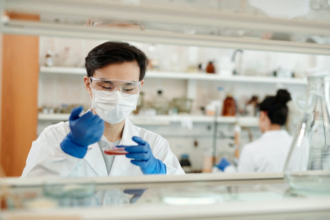 A lab technician transfers samples for testing.