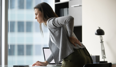 A woman clutching her lower back in pain after standing from her office chair.