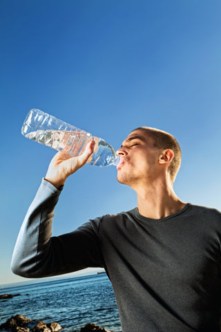 A man drinking a large bottle of water to stay hydrated while taking Delta-8