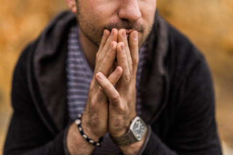 A man in need of natural anxiety remedies anxiously grasping his fingers together.