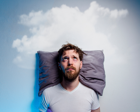 A man laying on a pillow awake due to insomnia
