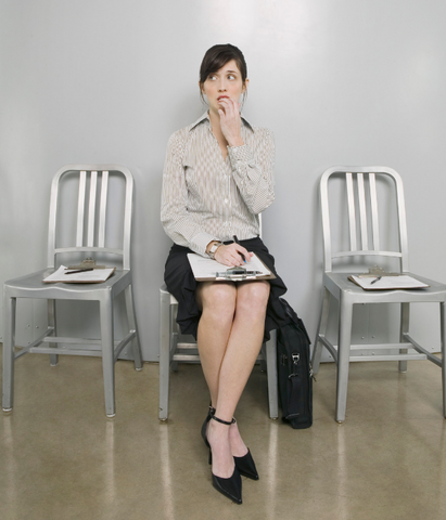 A woman dealing with a nervous stomach while waiting for an interview.