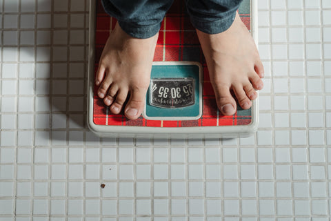 A man standing on a scale to determine his weight, a factor that helps determine how many CBD gummies you should take.