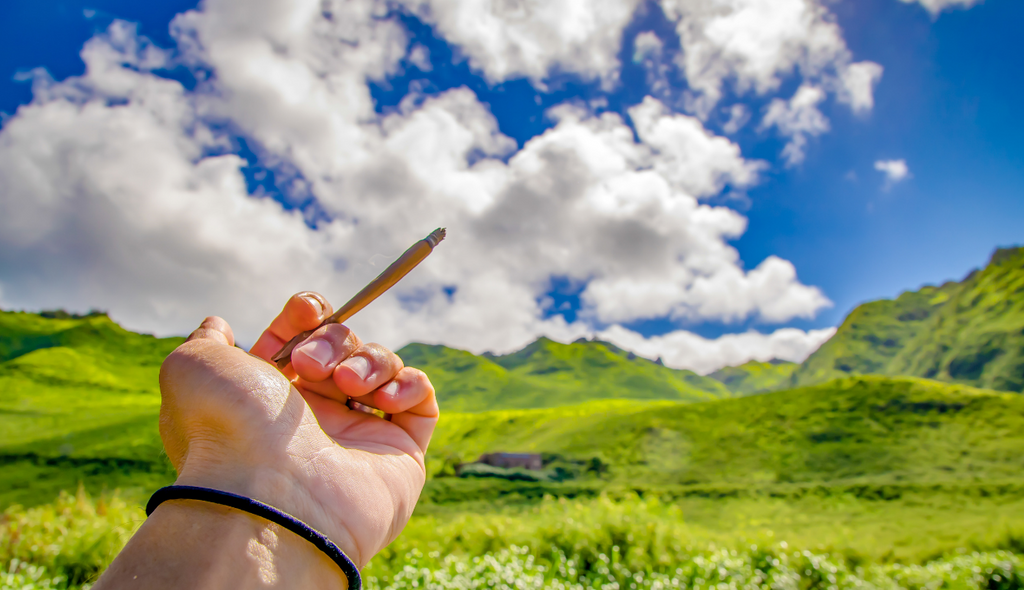 A person relaxing outdoors while smoking hand rolled Delta-8-THC flower.