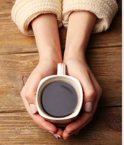 A woman nervously holding a cup of coffee.