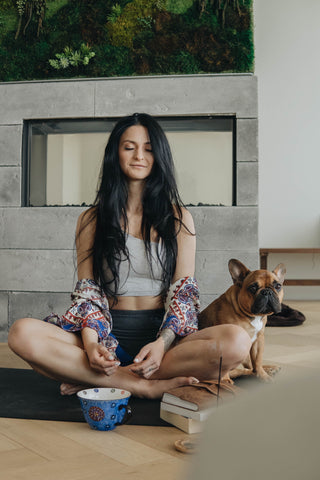 A woman meditating and deep breathing to help naturally reduce anxiety without medications.